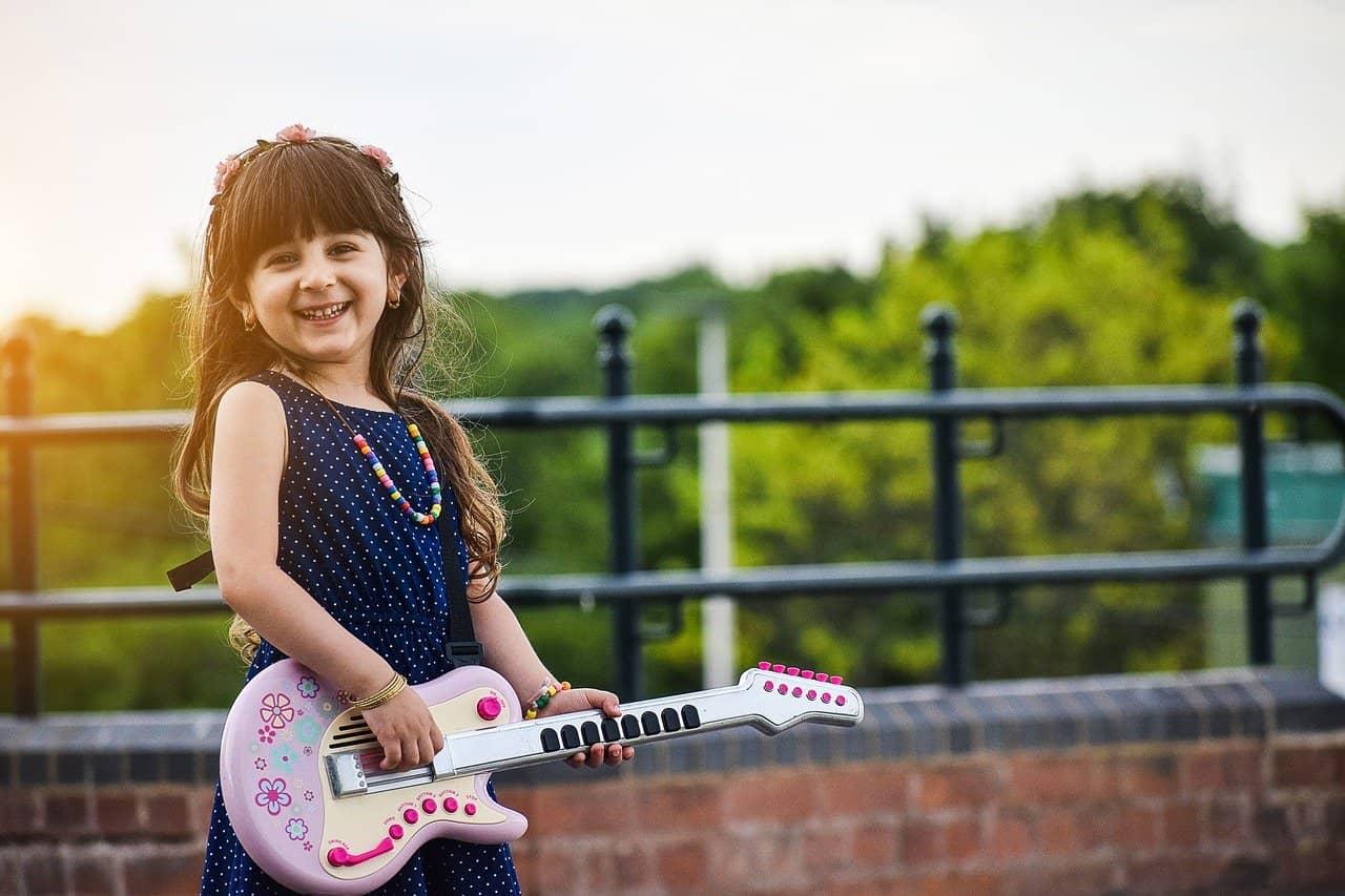 niña tocando guitarra de juguete
